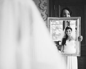 La sposa si guarda allo specchio con l'abito da sposa