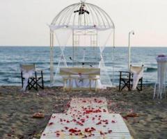 Allestimento della cerimonia in spiaggia con gazebo a forma di gabbia