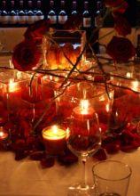 Centrotavola con rose rosse e candele per il tavolo degli sposi