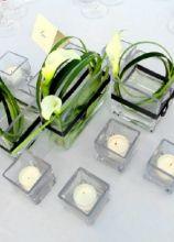 Particolare centrotavola creato con calle, candele e piccoli vasetto di vetro