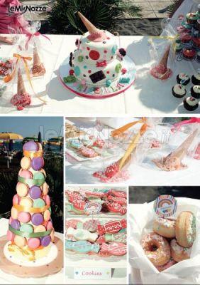 Dessert table-piramide di macarons, biscottini a forma di caramella e donuts