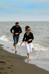 Sposi che corrono sulla spiaggia per il prefilm di matrimonio