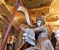 Arpista di Musica in Maschera con una maschera veneziana