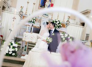 Il bacio degli sposi dopo la cerimonia con rito cattolico - WeddingPhotoStudio