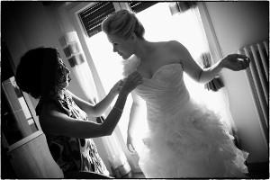 La sposa si fa aiutare per indossare il vestito - Alessandro Zanon Wedding Photographer