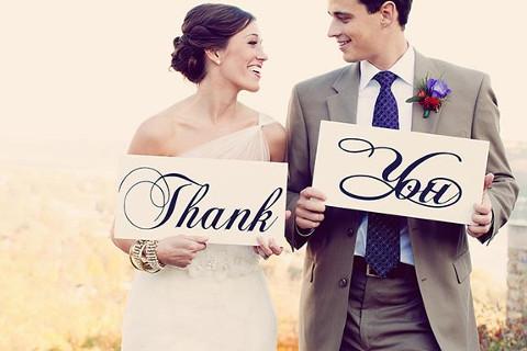 Sposi con un cartello con scritto