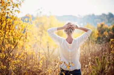 Una giovane donna che passeggia nella natura assolata