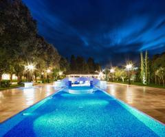 La piscina dell villa illuminata per un ricevimento di matrimonio serale