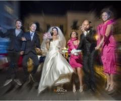 Foto effetto sfocato degli sposi con gli invitati