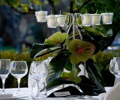 Allestimento con candele e anturium dei tavoli di nozze
