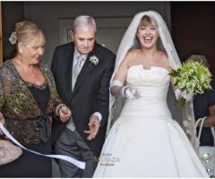 Fotografia della sposa che taglia il nastro all'uscita di casa