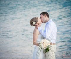Fotografia del bacio degli sposi in riva al mare