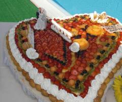 La torta di nozze a forma di cuore con frutta fresca