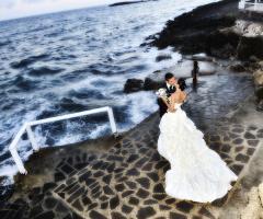 Foto del bacio degli sposi sugli scogli