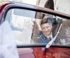 Foto degli sposi felici sulla macchina da cerimonia