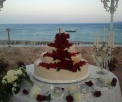 La torta nuziale decorata con petali di rosa