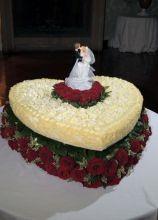 La torta di nozze a forma di cuore con rose rosse