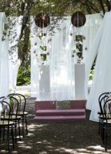 Allestimento floreale con stoffe bianche per la cerimonia in giardino