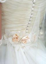 Abito da sposa con corpetto abbottonato e rose applicate sulla vita