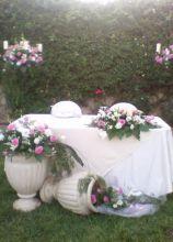 Il tavolo degli sposi con composizione di rose e anfore