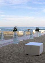 Decorazioni floreali con vasi di design per un matrimonio in spiaggia