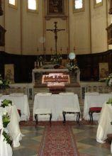 Allestimento con tessuti bianchi per i banchi della chiesa