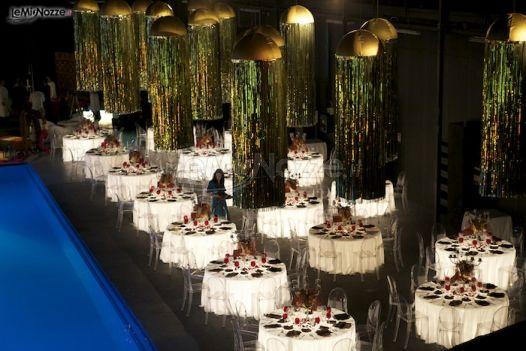 Tavoli rotondi sotto illuminati per il matrimonio a bordo piscina