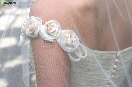 Rose in tessuto applicate alla spallina dell'abito da sposa